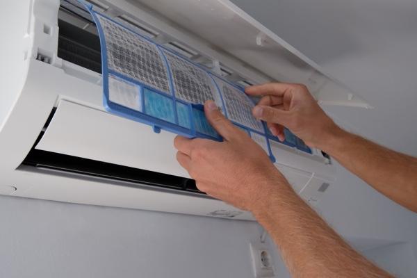 An HVAC technician repairing an air conditioner.