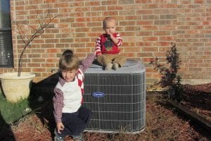 two kids sitting on and near ac unit
