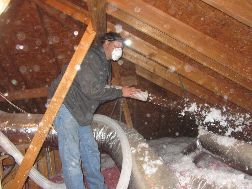 man blowing insullation in attic